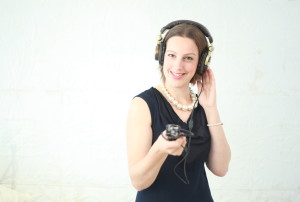 Ann wearing a dark blue dress and headphones, holding a recording device