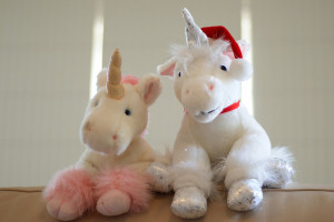 Two toy unicorns, one pink (l) and one white (r).